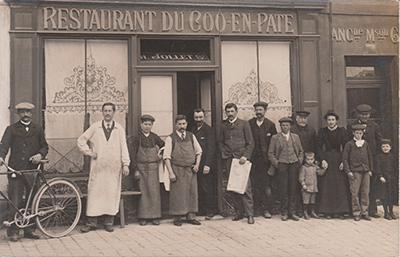 Carte postale 1900 de la façade d'une auberge nommée Restaurant du Coq en Pâte. L'équipe du restaurant pose devant la façade.